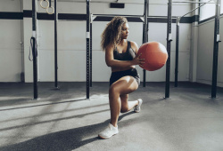 Young woman exercising with medicine ball in gym